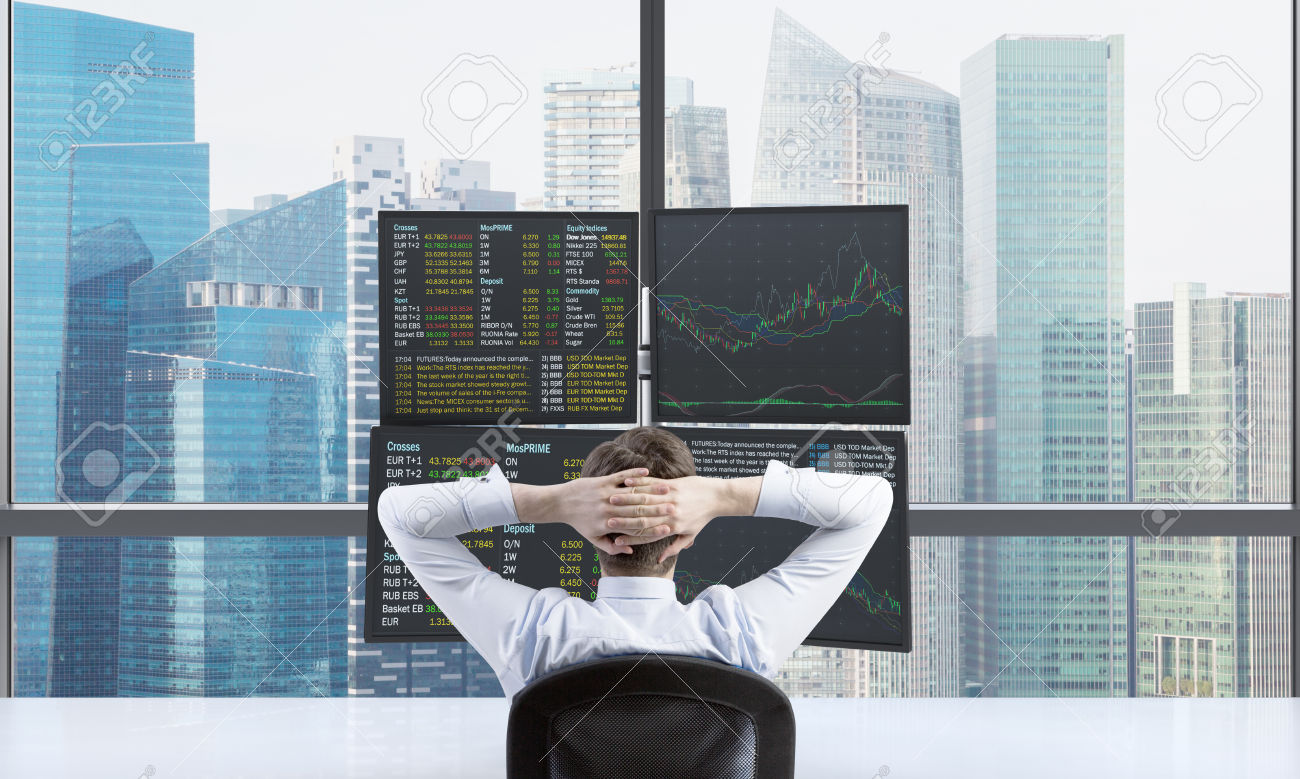 A rear view of relaxing trader who is waiting for a success of his position in front of trading station. Trading at forex market. Singapore panoramic view.